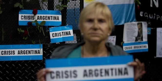 Une femme tient une pancarte