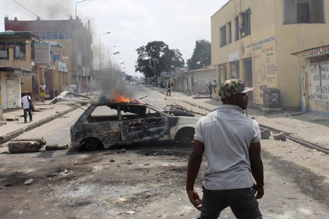 Un manifestant devant une voiture incendiée lors des violences du 20 janvier à Kinshasa.