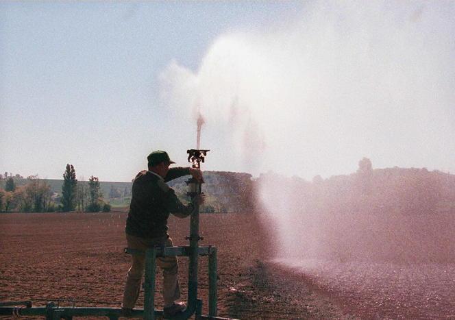 Un agriculteur règle son système d'arrosage, le 24 avril.