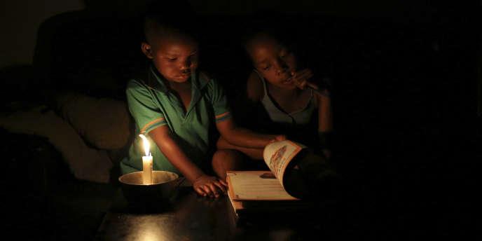 A Soweto, en Afrique du Sud, Sinovuyo Bhungane, 9 ans, fait ses devoirs à la bougie.