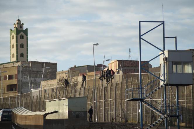 Des migrants tentent de franchir la barricade séparant l'enclave espagnole de Melilla du Maroc, le 30 décembre 2014.