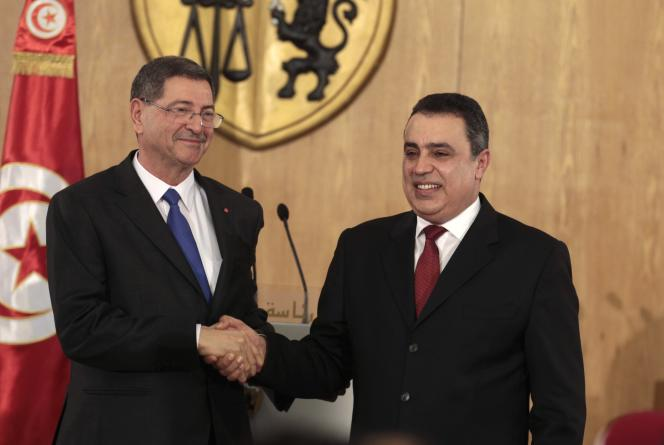 Cérémonie de passation des pouvoirs à Tunis le 6 février. Le nouveau premier ministre Habib Essid (à gauche) serre la main de son prédécesseur Mehdi Jomaa, lequel a négocié l'emprunt d'un milliard de dollars sur les marchés.