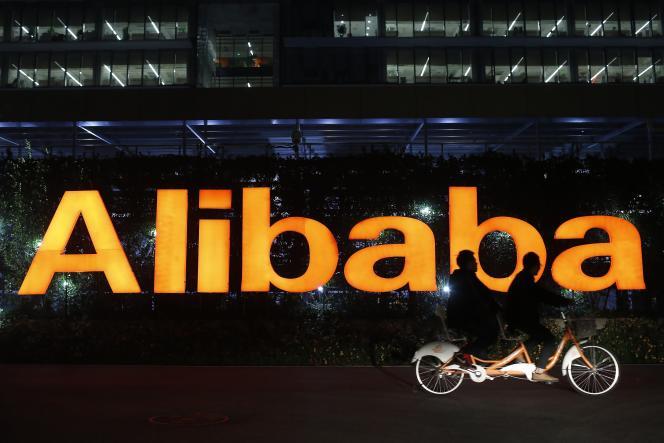Des gens font du vélo devant le siège du groupe Alibaba, àHangzhou, en Chine, en novembre 2014.