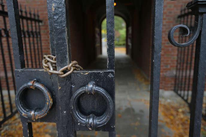 Une porte d'entrée de l'université Harvard fermée par des chaînes.