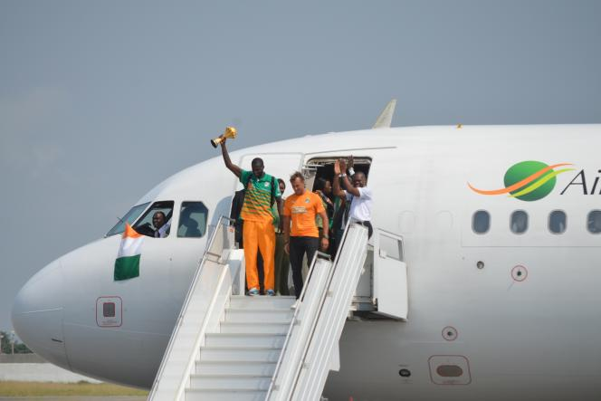 Le capitaine de la sélection ivoirienne, Yaya Touré, et le sélectionneur Hervé Renard brandissant le trophée de la CAN 2015, à leur arrivée à Abidjan, lundi 9 février 2015.