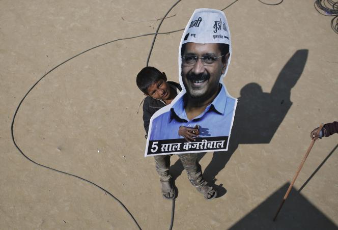 A New Delhi, le 10 février, unenfant brandit un portrait d'Arvind Kejriwal, candidat du « Parti de l'homme ordinaire » réélu à la tête du gouvernement de la capitale indienne.