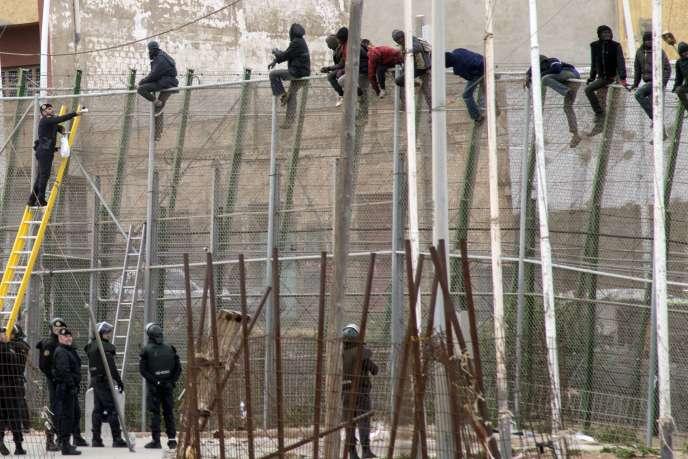 Un garde civil lance un sandwich à un migrant perché au sommet de la clôture entre le Maroc et l'enclave espagnole de Melilla, le 10 février 2015.