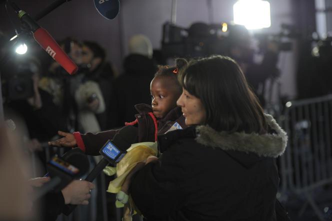 Un mère tient sa fille, originaire d'Haïti, à leur arrivée à Roissy, en décembre 2010.