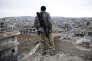 30 janvier 2015. Un combattant kurde syrien observe les ruines de Kobané.