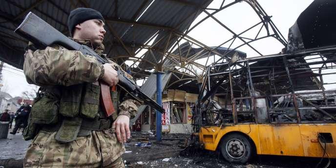 Un rebelle prorusse à proximité d'un des minibus détruits par un obus, le 11 février 2015.