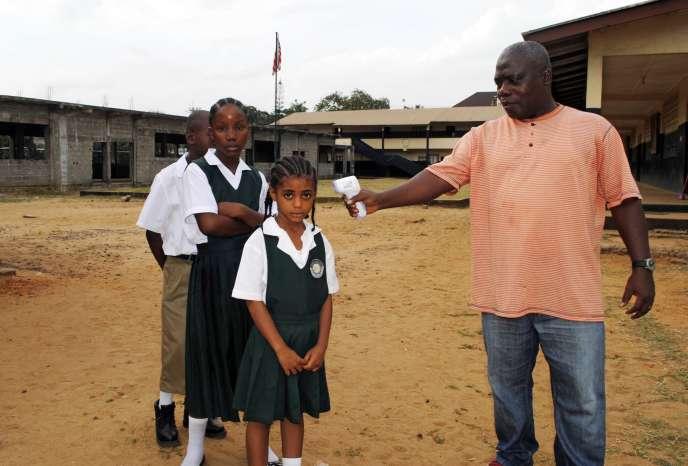 16 février à Monrovia (Liberia) : un homme vérifie la température corporelle d'une écolière.