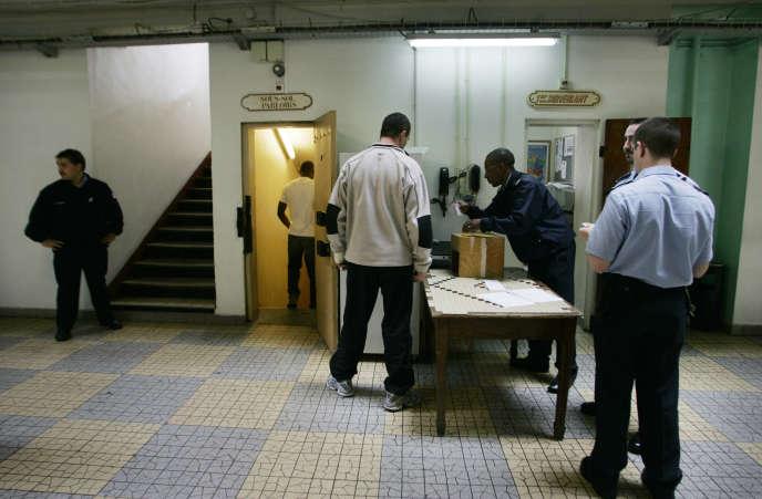 Des détenus passent un contrôle avant de descendre au parloir, le 4 juillet 2005, à la maison d'arrêt de Fresnes.