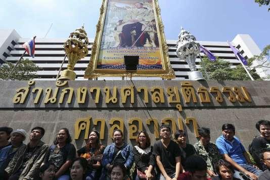 Des proches et défenseurs de Patiwat Saraiyaem et de Porntip Mankong chantent devant une image du roi Bhumibol Adulyadej, après leur condamnation pour lèse-majesté, à Bangkok, en février.