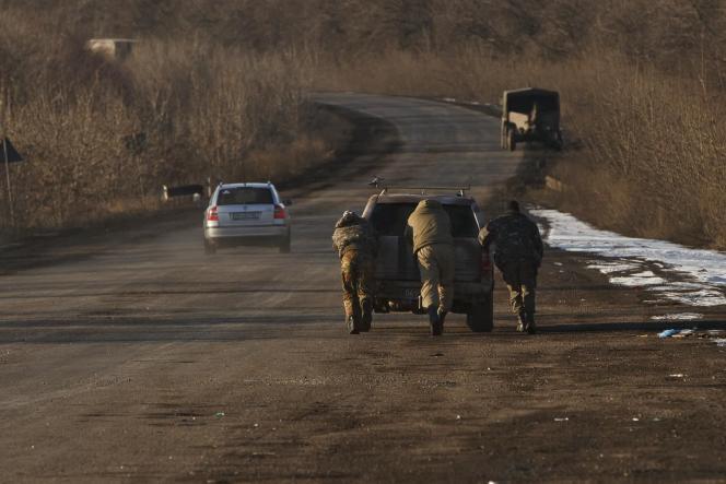 Des troupes ukrainiennes poussent une voiture pour la faire démarrer en sortant de Debaltsevo.