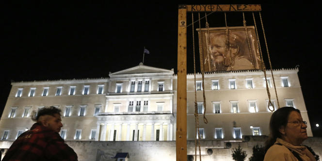Une image d'Angela Merkel est suspendue devant le parlement grec, en novembre 2012, la veille d'un vote crucial.
