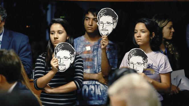 A Brasilia, des citoyens brandissent des portraits du jeune agent lors d'auditions du Sénat brésilien sur les écoutes de la NSA. Les documents dévoilés par Edward Snowden ont révélé que les Etats-Unis avaient espionné la présidente brésilienne, Dilma Rousseff.