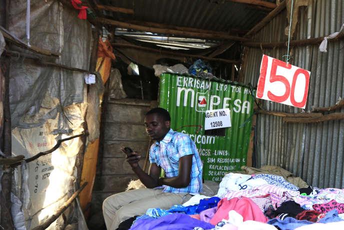 Brian Ochieng attend des clients de M-Pesa dans sa friperie de Kibera, à Nairobi, le 31 décembre 2014.