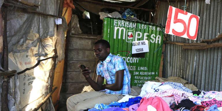 Une échoppe de vêtements de seconde main à Nairobi, au Kenya, où l'on peut payer grâce au système M-Pesa, le moyen de paiement par SMS, en décembre 2014.