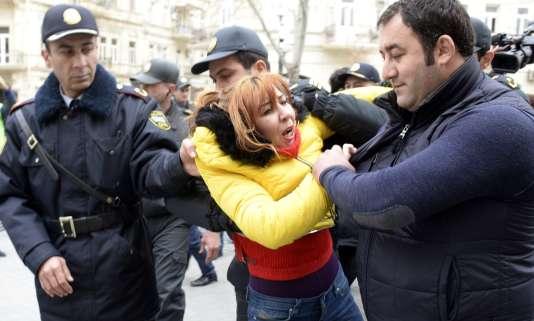 Des policiers azeris ceinturent une activiste au cours d'une manifestation contre la dévaluation de la monaie nationale, le manat, en 2015. Entre 2014 et 2016, la chute du prix du barril a diviser par deux le PIB du pays, impactant la vie quotidienne des habitants.