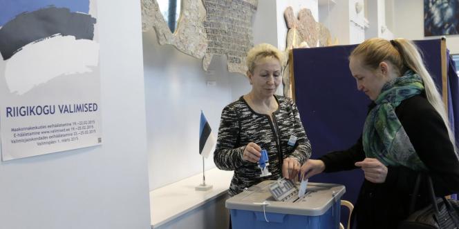 Une électrice dépose son bulletin dans l'urne à l'occasion des élections législatives estoniennes, le 1er mars, à Torva.