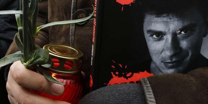Un homme tient une bougie votive et le portrait de Boris Nemtsov en couverture du magazine russe