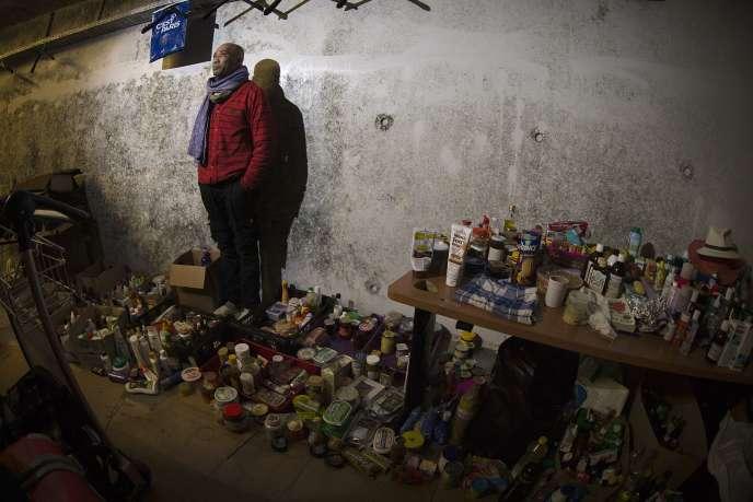 Patrice, un mal-logé de 44 ans, pose dans son squat à l'aéroport de Paris-Charles de Gaulle, au milieu des objets qu'il a collectés auprès des voyageurs.