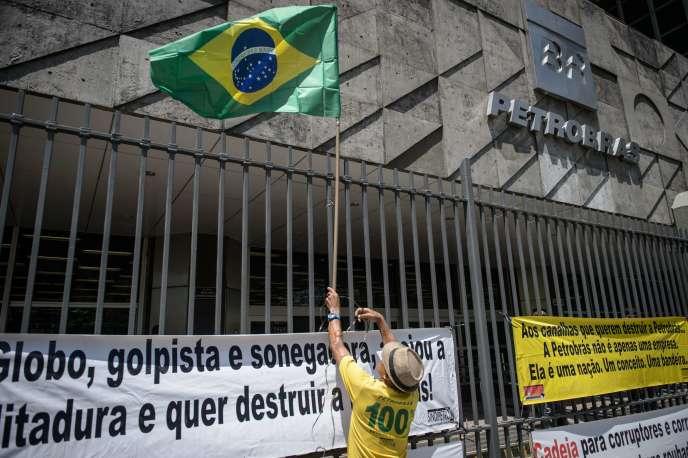 Un manifestant attache un drapeau brésilien au grillage entourant le siège de Petrobras, le 4mars à Rio de Janeiro.