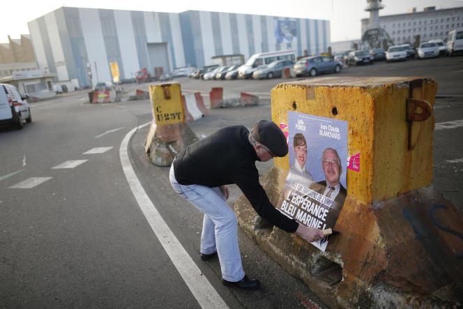 Jean-Claude Blanchard, candidat du Front national, en plein collage d'affiches devant les chantiers navals de Saint-Nazaire, le 11 mars.