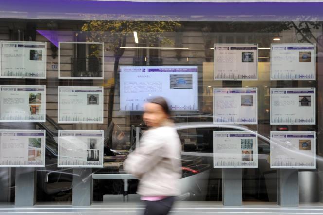 Une personne passe devant une agence immobilière à Paris.