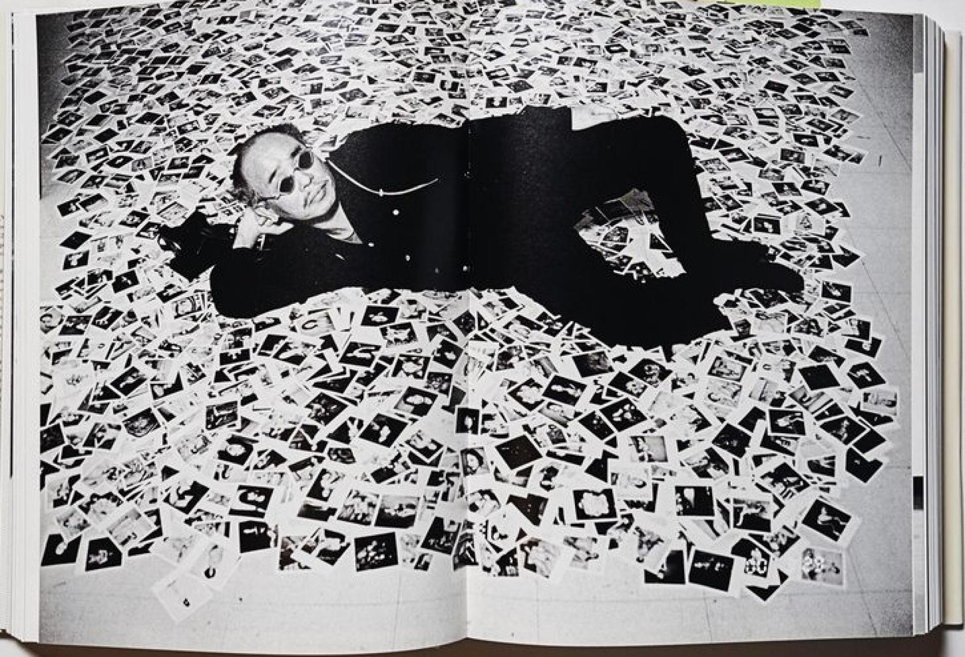Araki, allongé sur 6 000 de ses clichés  pour l'exposition « Polart 6000 », en 2009.