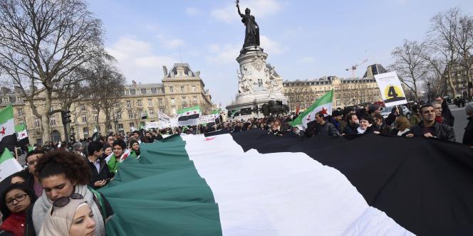 Des jeunes gens ont brandi un immense drapeau de la révolution syrienne, samedi 14 mars, place de la République à Paris.