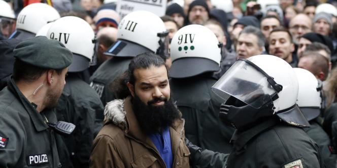 Des policiers encadrent un manifestant salafiste à Wuppertal, le 14 mars.