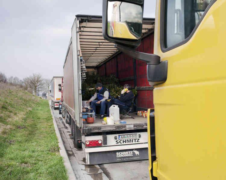 A l'arrière d'un camion rouge transportant des plantes, deux hommes discutent : Alexandru, 45 ans, est originaire d'Arad, une ville de Transylvanie, dans l'ouest de la Roumanie ; Laurenciu, 50 ans, de Petrosani, dans la même région.