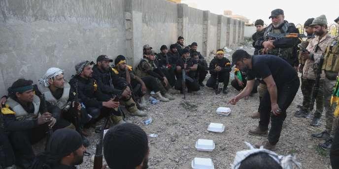 Des combattants chiites des Brigades d'Ali vérifient leur plan de bataille à Tikrit, le 14 mars.
