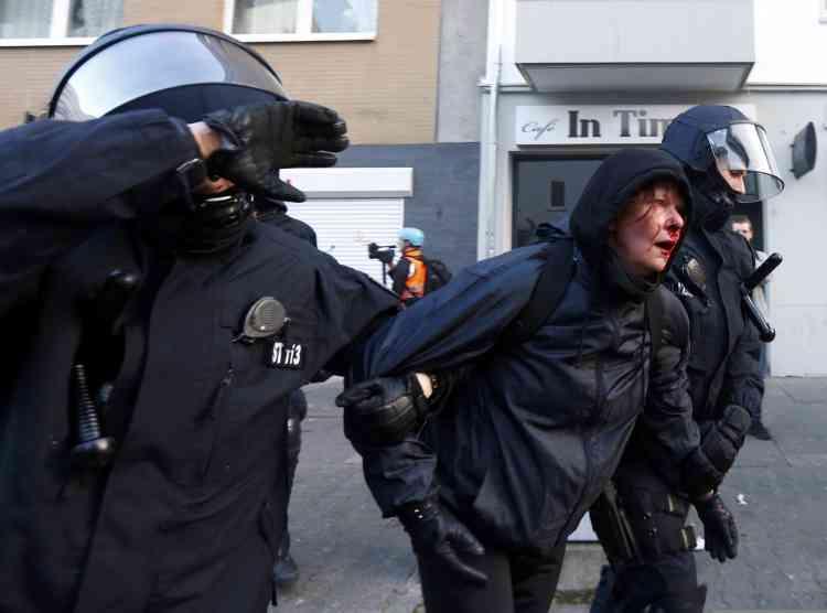 Des policiers arrêtent un manifestant blessé dans les affrontements avec les forces de l'ordre.