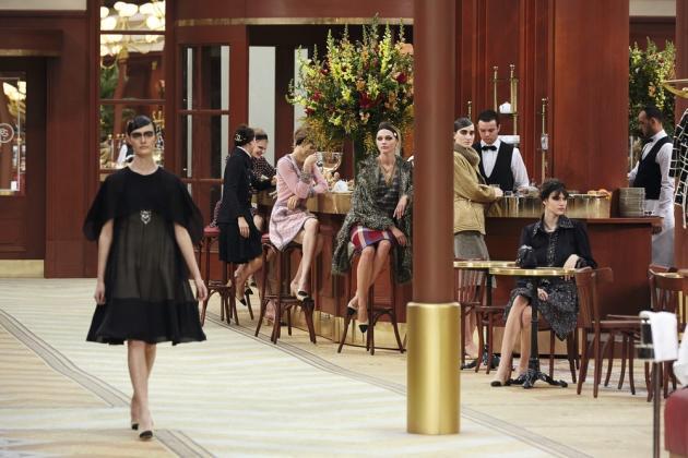 Cette année, Chanel recevait l'internationale de la mode dans une brasserie  aux dimensions de la nef du Grand Palais. Un grand barnum qui se moque du bon goût et  des tendances. La mode, elle, était d'un chic fou. Silhouettes germanopratines en tweed graphique, belles mailles portées sur des jupes pied-de-poule longueur genou, tailleurs en cuir matelassé et souliers bicolores, la grammaire Coco ou le charme contemporain de la bourgeoisie.