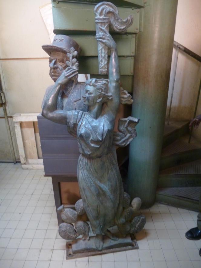 En bas d'un escalier des Archives nationales du Sénégal, ces deux sculptures montent la garde. Les pieds de Marianne sont entourés de neuf manguiers représentant chacun une colonie.