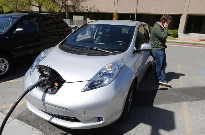 Justin Miller makes a phone call as he charges his 2013 Nissan Leaf electric car at ABB Inc.'s DC fast charging station in Salt Lake City, Utah, in this April 30, 2014 file photo.  Automakers are readying a new generation of mass-market electric cars with more than double the driving range of today's Nissan Leaf, betting that technical breakthroughs by big battery suppliers such as LG Chem will boost lackluster demand.   REUTERS/George Frey/Files
