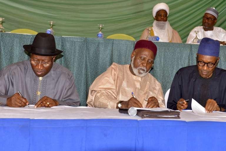 "Le président sortant, Goodluck Jonathan (à gauche) et l'actuel chef d'Etat, Muhammadu Buhari (à droite), signent un ""accord de paix"" le 26 mars 2015."