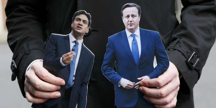 Un journaliste pose avec les portraits d'Ed Miliband et de David Cameron, à Londres, le18mars.