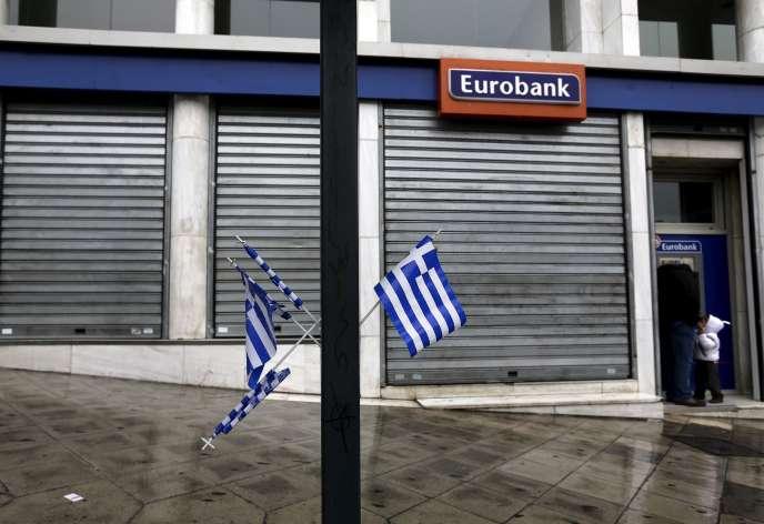 Devant une agence Eurobank, dans les rues d'Athènes, le jour de la fête de l'indépendance, mercredi 25mars.