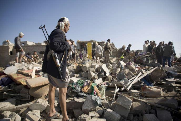 Un soldat houthiste monte la garde sur les ruines d'une maison détruite par les bombardements de la coalition arabe sous bannière saoudienne près de l'aéroport de Sanaa, au Yémen, le 26 mars 2015.