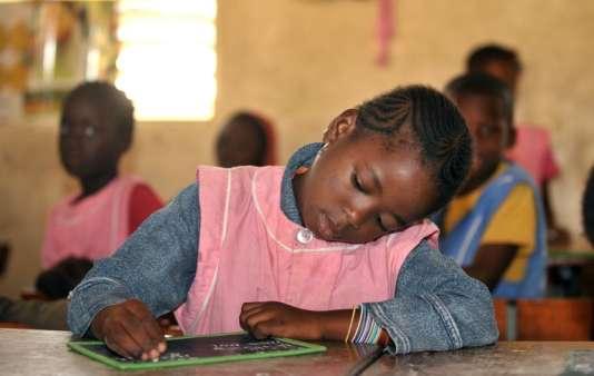 Une jeune écolière sénégalaise, une plaque d'ardoise devant elle, suit un cours de français le 11 mars 2010, dans une école de Médine à Dakar.