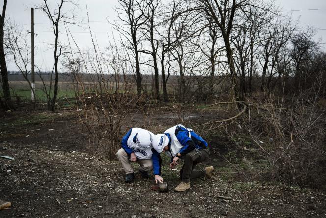 Des observateurs de l'OSCE regardent les fragments d'un missile antitank aux abords d'un village près de Marioupol.