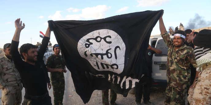 Des soldats des forces de sécurité irakiennes tiennent un drapeau d'un groupe de l'organisation Etat islamique, à Tikrit, au nord de Bagdad, en mars 2015.