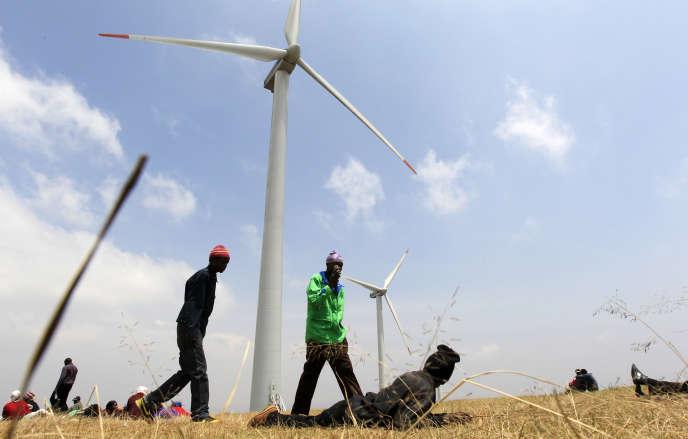Des hommes marchent dans un champ d'éoliennes installées sur les collines de Ngong, à une vingtaine de kilomètres de Nairobi (Kenya)