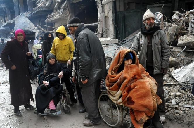 Des habitants attendent à l'entrée du camp de recevoir de l'aide des Nations unies, le 4 février 2014.