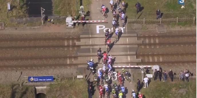 Des coureurs du Paris-Roubaix franchissent un passage à niveau avant le passage d'un TGV