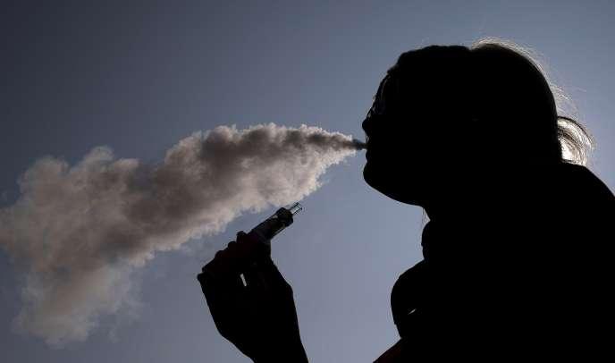 Une femme vapote sa cigarette électronique.