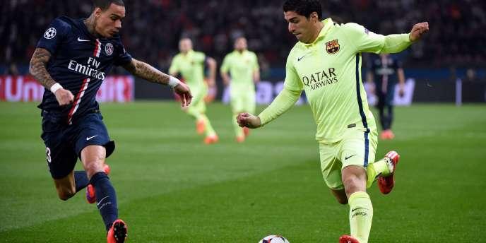 L'attaquant du FC Barcelone Luis Suarez (à droite), auteur du deuxième but contre le PSG, ici face au Parisien Gregory Van Der Wiel, en quart de finale aller de la ligue des champions, le 15 avril.